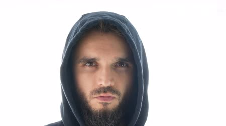 Close-up of serious thoughtful bearded man face in hoodie looking at you, studio isolated on white background. Dostupné videozáznamy