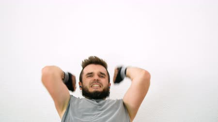 Determined young bearded man punching and exercising abs, isolated on white background. Dostupné videozáznamy