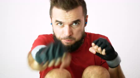 Young bearded man exercising abs and punching, isolated on white background.