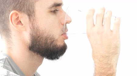 Profile of young bearded man face drinking glass of water, hi-key studio isolated on white background.