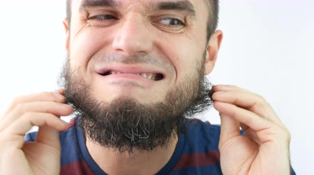 Close-up of angry bearded man face touching his beard, studio isolated on white background.