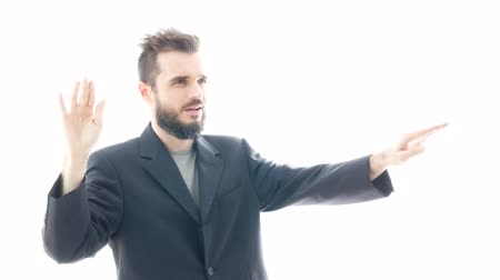 Self-confident bearded man in suit gesturing and enjoying contemporary music, hi-key studio isolated on white background.