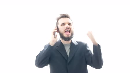 Excited successful bearded businessman on the phone gesturing, hi-key studio isolated on white background. Dostupné videozáznamy