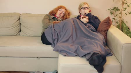 Exhausted girlfriends having a cold resting together under the blanket on the sofa at home. Dostupné videozáznamy