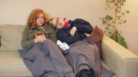 Sleepy girlfriends having a cold resting together under the blanket on the sofa at home.