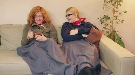 Happy girlfriends resting together under the blanket on the sofa at home.