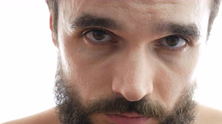 Close-up of serious bearded man face with brown eyes looking at you. Dostupné videozáznamy