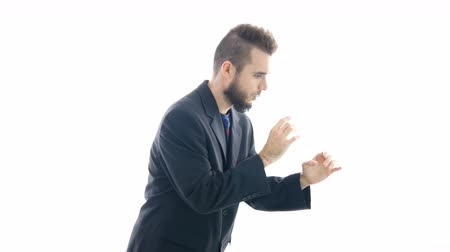 Funny bearded man in suit imitating play on wind instrument, studio isolated on white background. Dostupné videozáznamy