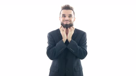 Funny bearded man in suit grimacing, touching his beard and looking at you, studio isolated on white background. Dostupné videozáznamy