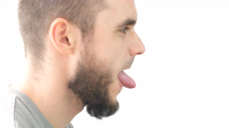 Profile of crazy bearded man face sticking his tongue and grimacing, studio isolated on white background. Dostupné videozáznamy