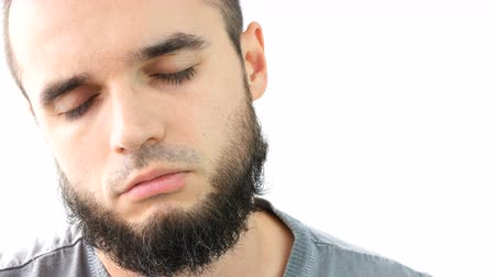 Close-up of young bearded man face sleeping and waking up, studio isolated on white background.