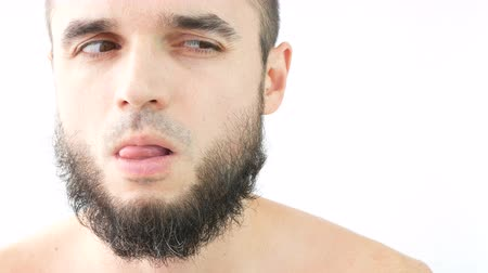 Close-up of naked bearded sly prankster making funny faces, studio isolated on white background.