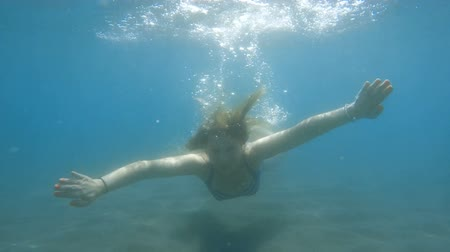 Underwater slow-motion of young woman diving in the ocean. Dostupné videozáznamy