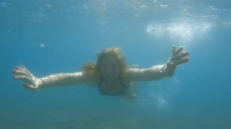 Underwater slow-motion of a woman free diving and swimming in the ocean.