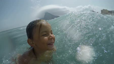 Beautiful happy girl enjoying sea waves and summer vacation in Andalusia, Spain.