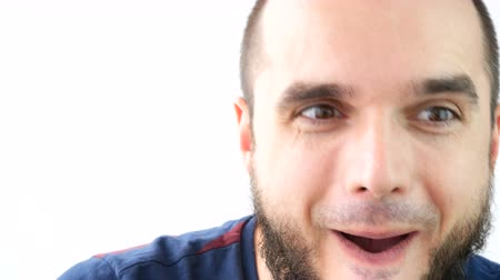 Close-up of crazy bearded man face grimacing and making funny faces, studio isolated on white background.