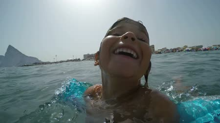 Close-up of happy girl with inflatable armbands enjoying sea and summer vacation in Andalusia, Spain.