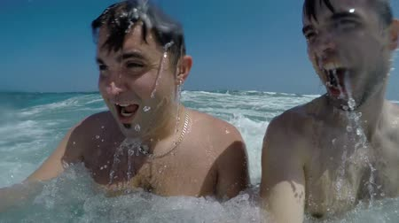 Slow-motion of two excited men enjoying summer in the waves of heavy Alboran Sea in Andalusia, Spain.