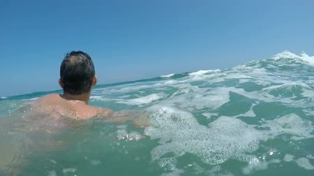 Back view of a man swimming in the waves of Alboran Sea in Andalusia, Spain.