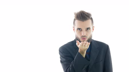 Happy bearded man in suit sending a kiss to you, studio isolated on white background. Dostupné videozáznamy