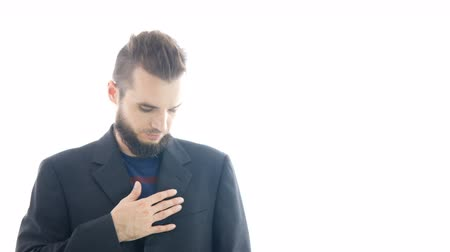Serious bearded man in suit checking and adjusting his outfit, studio isolated on white background.