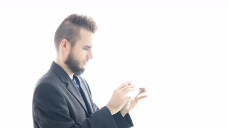 Young bearded man in suit using a smartphone, hi-key studio isolated on white background.