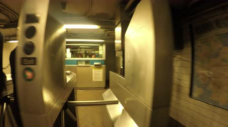 New York City, USA - 20 May 2015: People walking through turnstiles and corridor inside New York City Subway station on Manhattan.