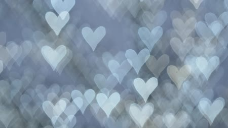 cold white lights on defocused blue background in a form of glimmering hearts Stock Footage