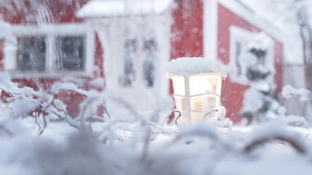 heavy snowfall with red house defocused in the background