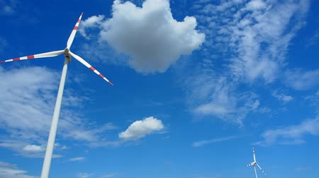 two windmills rotating during windy summer cloudy day with cloudy blue sky as a background Stock Footage