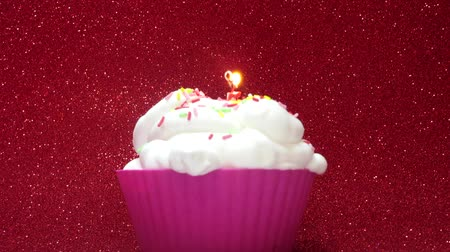 queque : Cupcake with a candle on a bright red background Vídeos