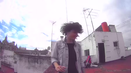 tüy : Beautiful woman on the roof of a building shaking her hair in slow motion