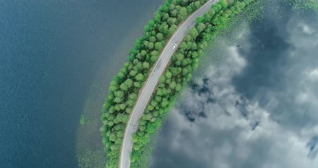 Финляндия : cPunkaharju Finland, cars drive past on a very narrow road surrounded by water