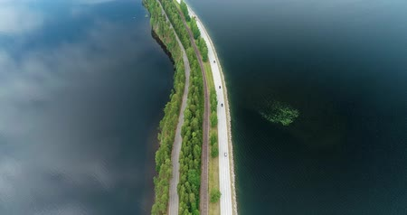 water rail : Punkaharju Finland, drone flying over a very narrow land part between lakes and water on both side said and roads and rail tracks on a summer day Stock Footage