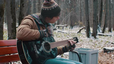 people in the Park playing guitar in winter