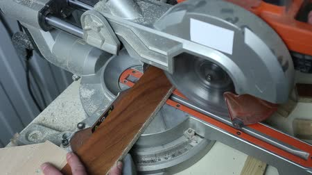 plywood : Circular saw saws parts. Sawed wood at the factory. Shut. furniture production. Male hands drinking the pieces on factory.