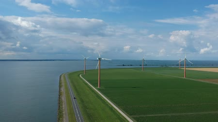 Флеволанд : Aerial shot of a Dutch dike and a power generation of windmills in the polder of Flevoland (Almere Pampus) on a cloudy windy day. Стоковые видеозаписи