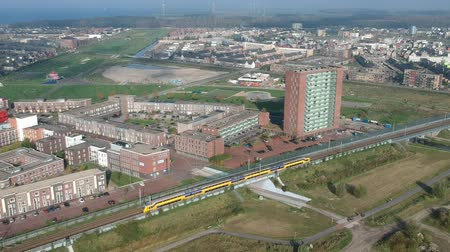Флеволанд : Aerial view of a passing train in the city of Almere Poort. Стоковые видеозаписи