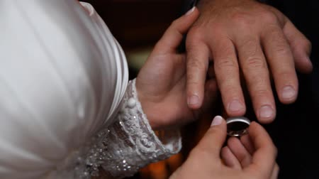 casamento : Bride putting a wedding ring on grooms finger