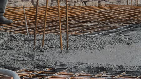 betoniarka : Concrete pouring works during commercial concreting floors; laborer compacting liquid cement into reinforcement form work