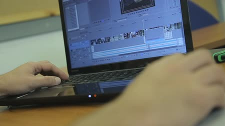bewerken : Man aan het werk op laptop met video-editing software Stockvideo