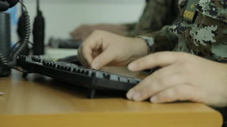 asker : Soldier typing on computer keyboard in communication center