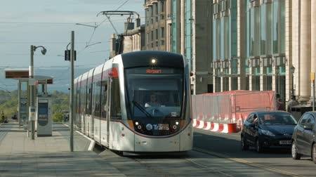skotsko : An Edinburgh tram leaves its stop towards the camera in St Andrew square, Edinburgh on a bright sunny day.