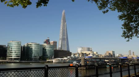 význam : Static shot of The Shard, City Hall and HMS Belfast taken from the north bank of the Thames. Footage is 4K original and shot on a clear sunny autumn morning. Framed by the leaves of a tree to the top and right