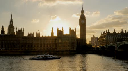 tower bridge : Thames river boat passes under Westminster Bridge as the sun sets behind parliament. Shot in 4K Stock Footage