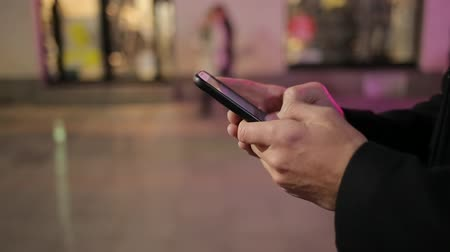 insan eli : A man in a black coat stands in a city street and quickly types a message on his smart phone as people pass by Stok Video
