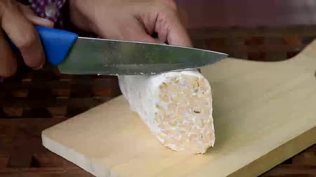 шалот : video footage hand slicing tempe at cutting board