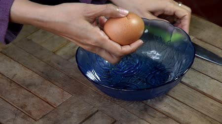 потребитель : video footage, hand egg shell breaking with stainless steel knife and then drop it into blue glass bowl