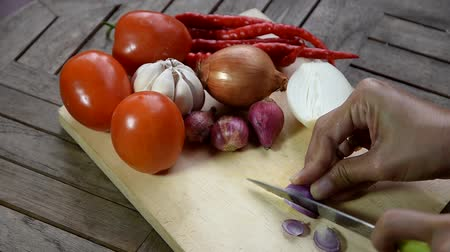 шалот : Shallots, garlic, onions, and chili peppers on a wooden cutting board Стоковые видеозаписи