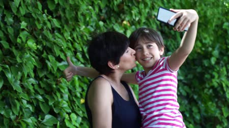 Little daughter and her mother taking selfie photo.